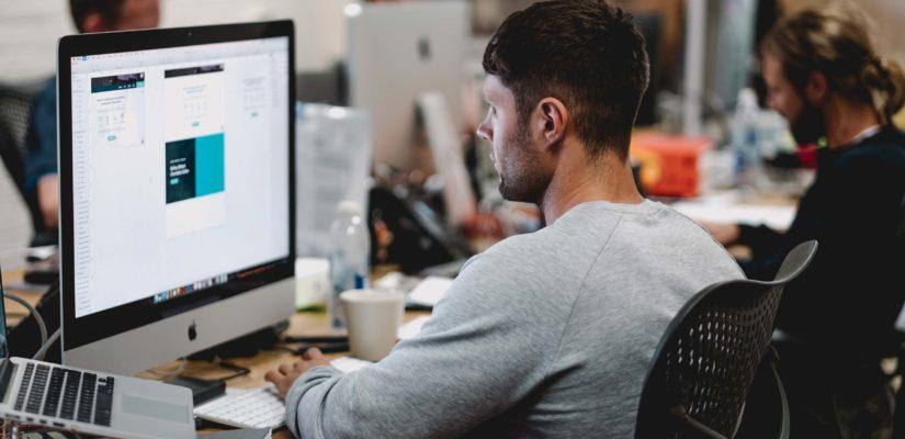 Mann arbeitet in Büro an Mac mit Arbeitstools
